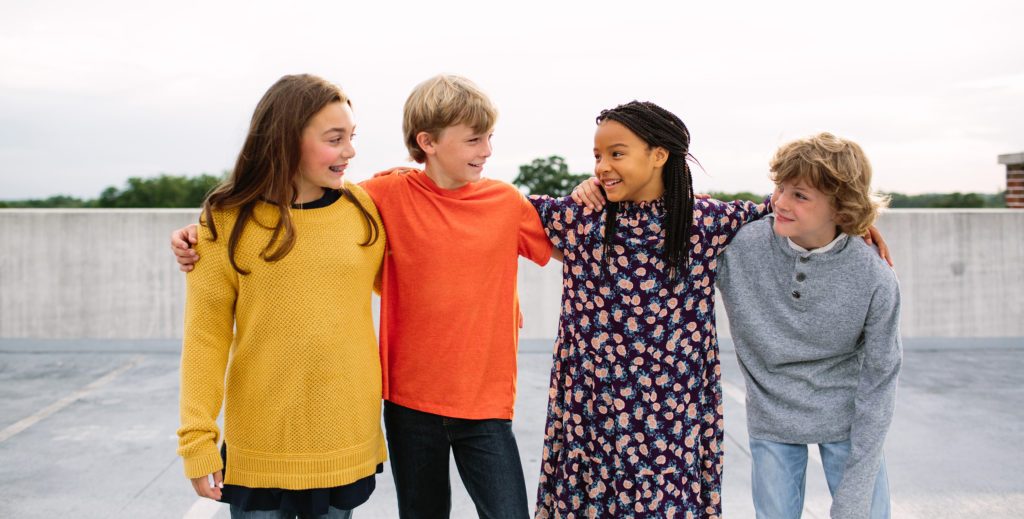 Four pre-teens or young teens standing in a line hanging out, smiling together