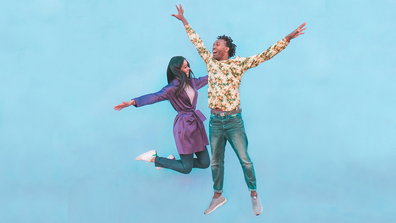 Happy black couple jumping in the air against a light-blue, plain background