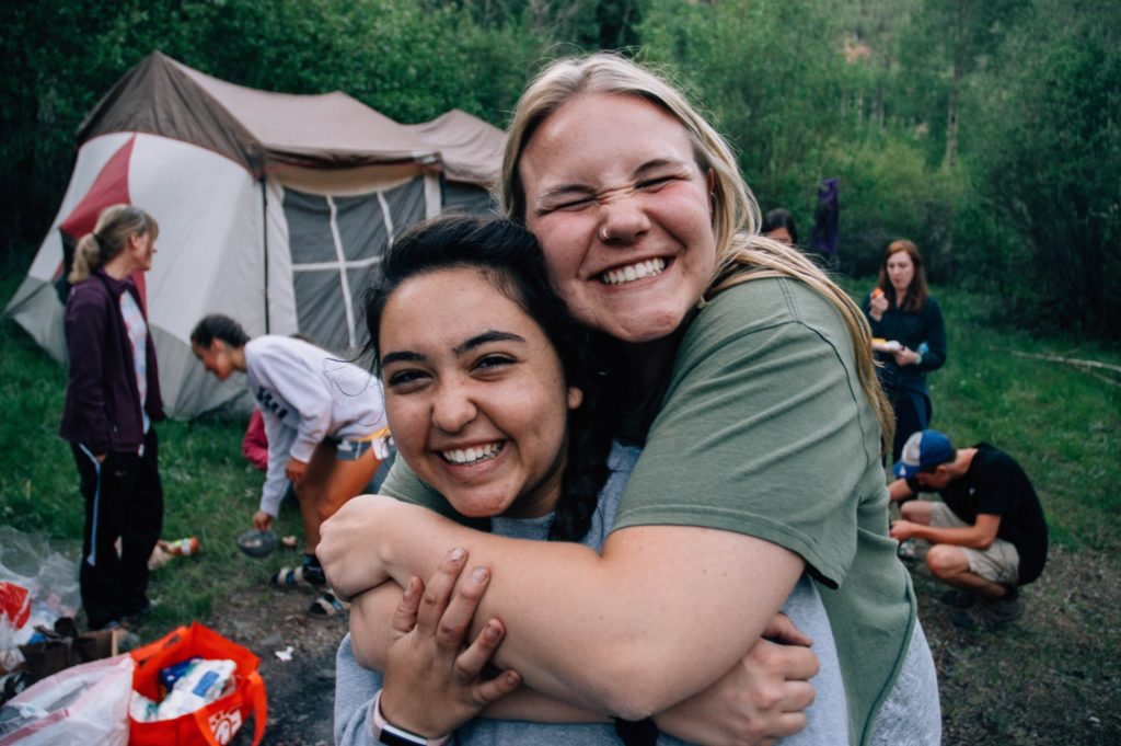 Two smiling teen girls outside at a campsite. One is enthusiastically and tightly hugging the other from behind.