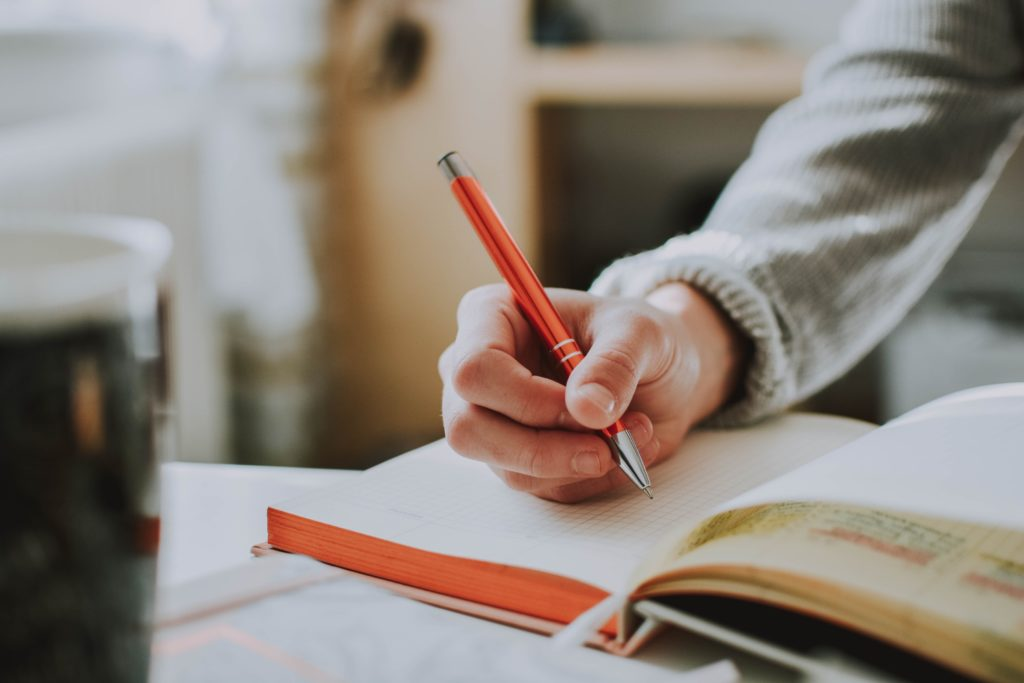 A man is writing in a journal to stay connected to his family through a journal.