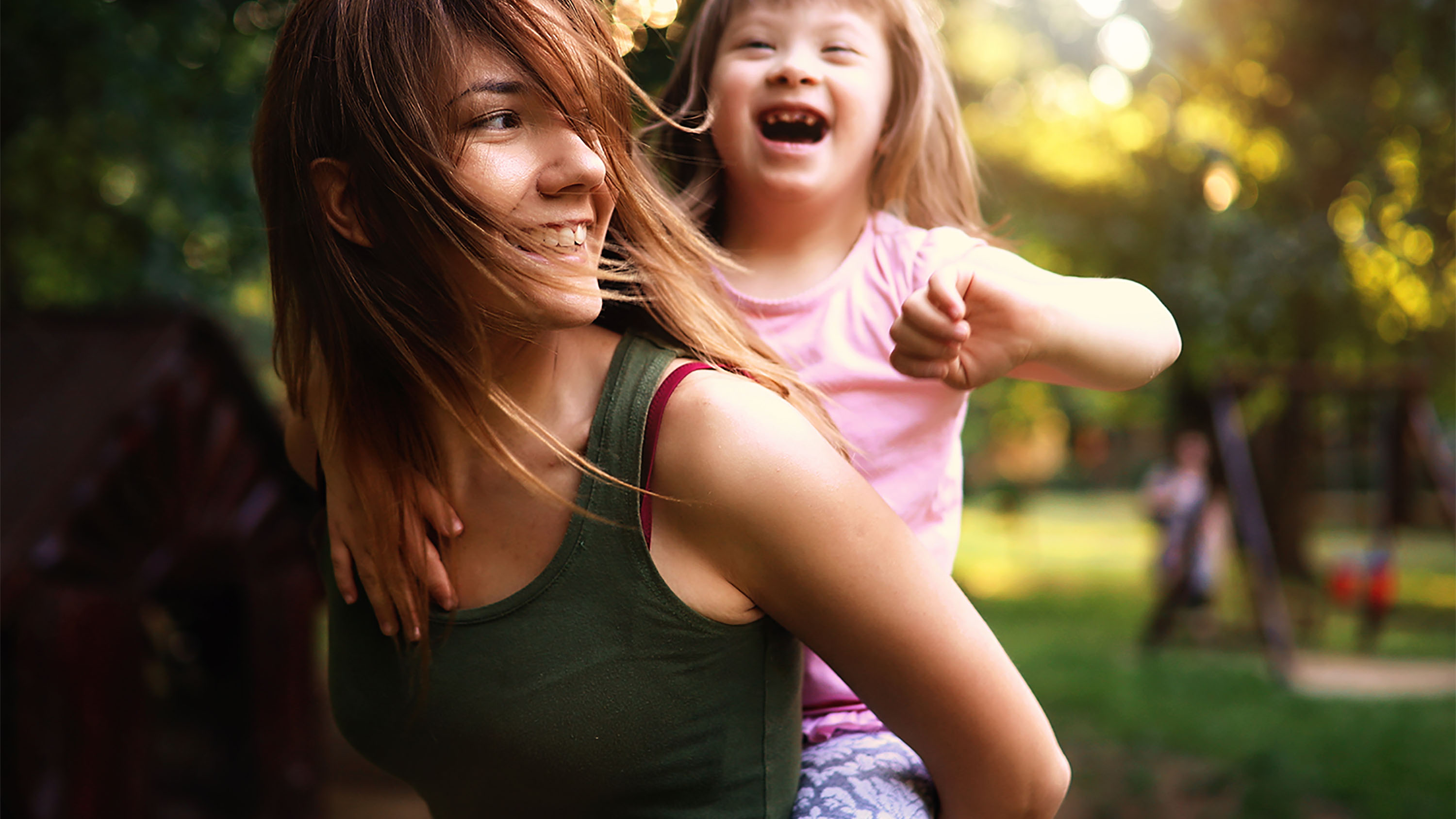 A woman demonstrates God's love for the disabled. Little girl with special needs enjoy spending time with mother