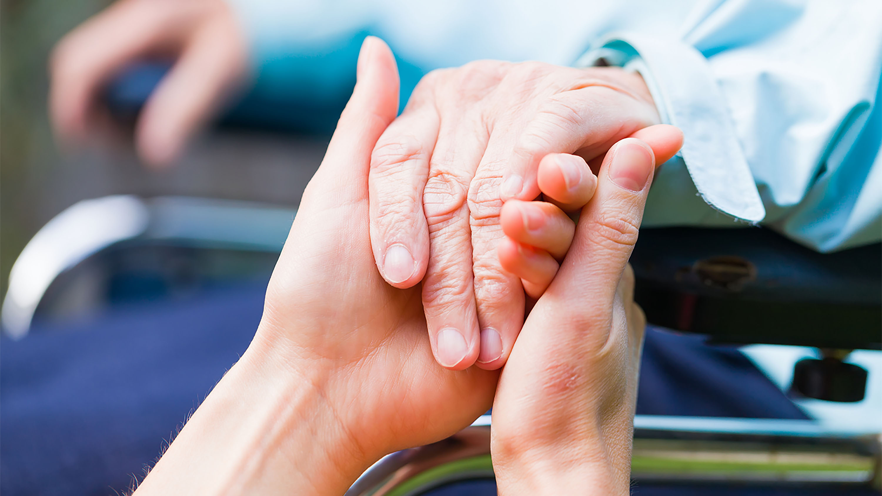 two young hands hold the older hand of someone in a wheelchair