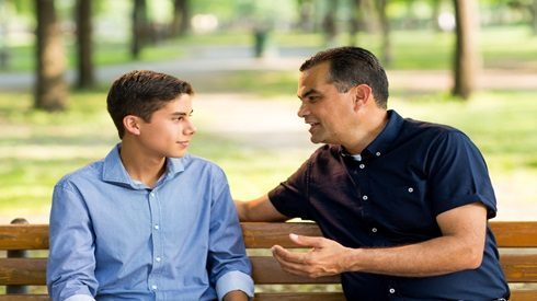 Father talking to teen son while sitting on a bench in a park