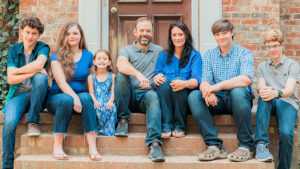 Family of seven sitting on porch steps