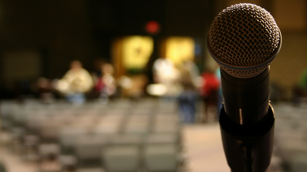 Close up of microphone with mostly empty auditorium in the background