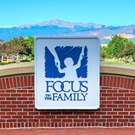 Focus on the Family welcome sign at the main entrance, showing Pike's Peak in the background on a clear summer day
