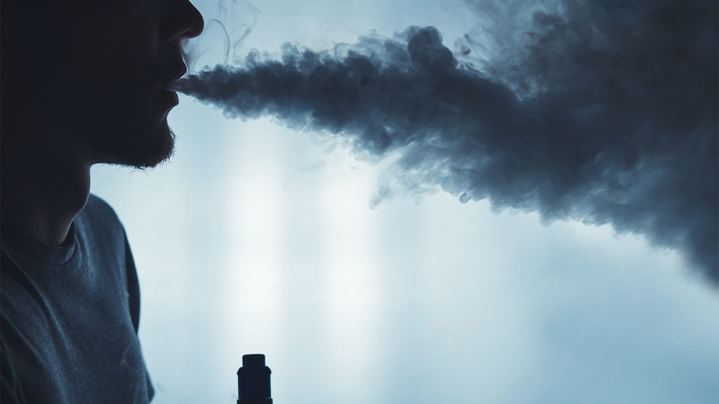 A bearded man in the clouds of steam from electronic cigarette closeup. vaping man