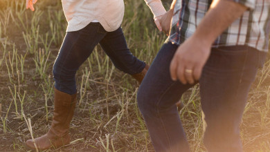 Close up of the legs of a married couple walking through a field. They're both wearing jeans and holding hands.