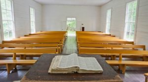 a bible is open on a pulpit in front of an empty church