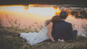 a newly married couple gazes on a pond at sunset