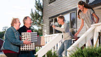 Happy grandparents arriving to their grandkids' home with presents in hand while two happy grandkids run out to meet them