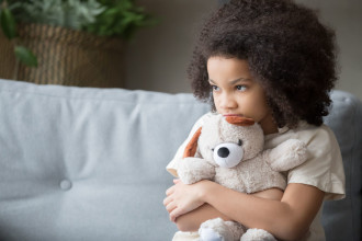 Sad-looking, young African-American girl sitting on a couch, hugging her teddy bear