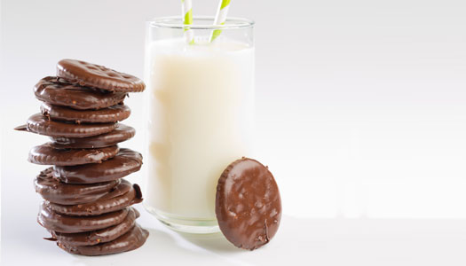 Homemade Thin Mints stacked next to a tall glass of milk