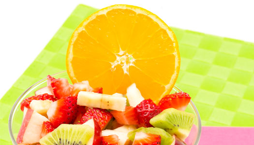 Close up of a coloful bowl of fruit salad with a big orange slice as a centerpiece