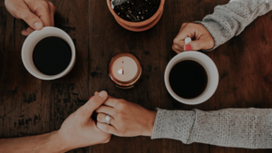 A man and woman hold hands and share coffee