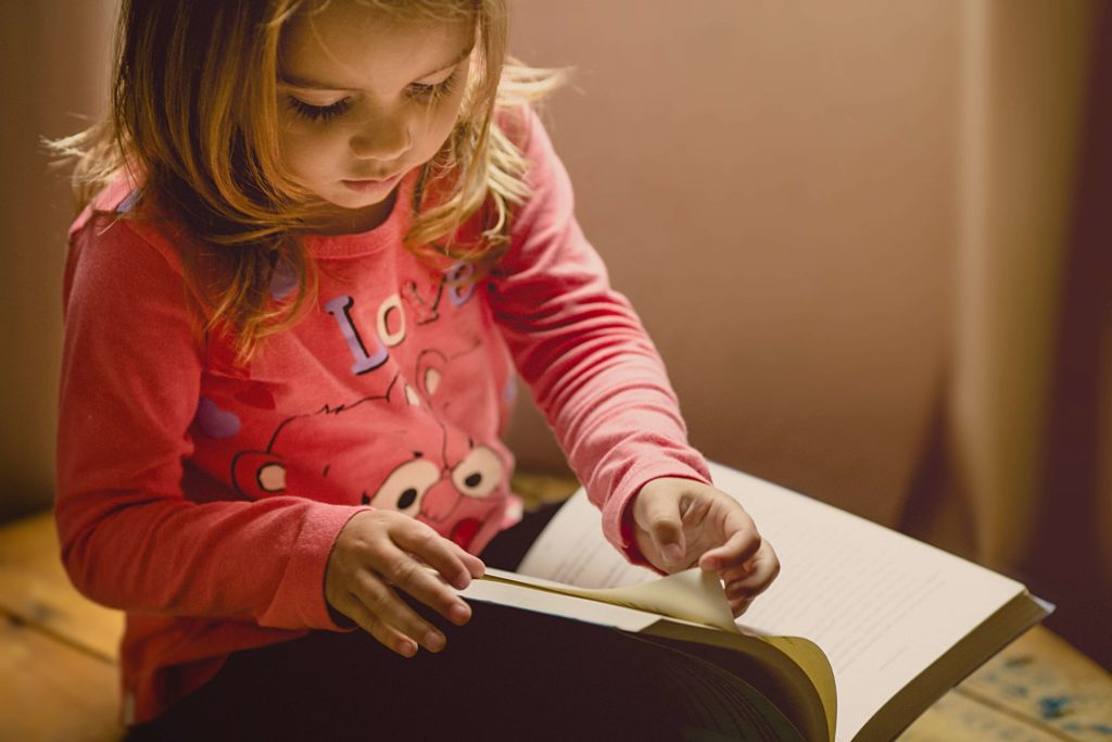 Young girl sitting on her bed flipping through a book