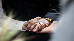 a man and woman hold hands during a wedding