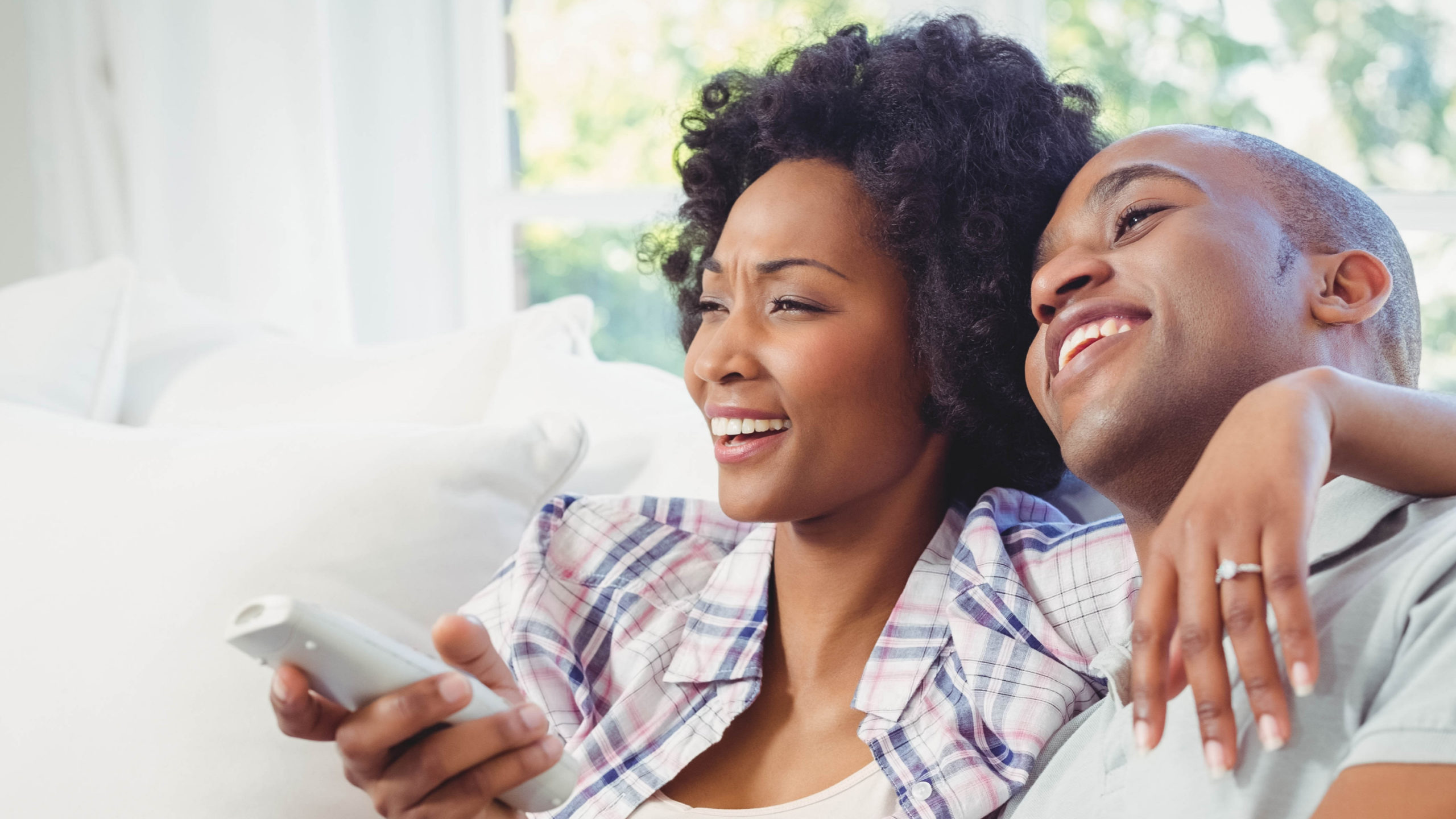 A couple laughs while watching TV