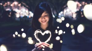 Older girl smiles as she holds an illuminated heart