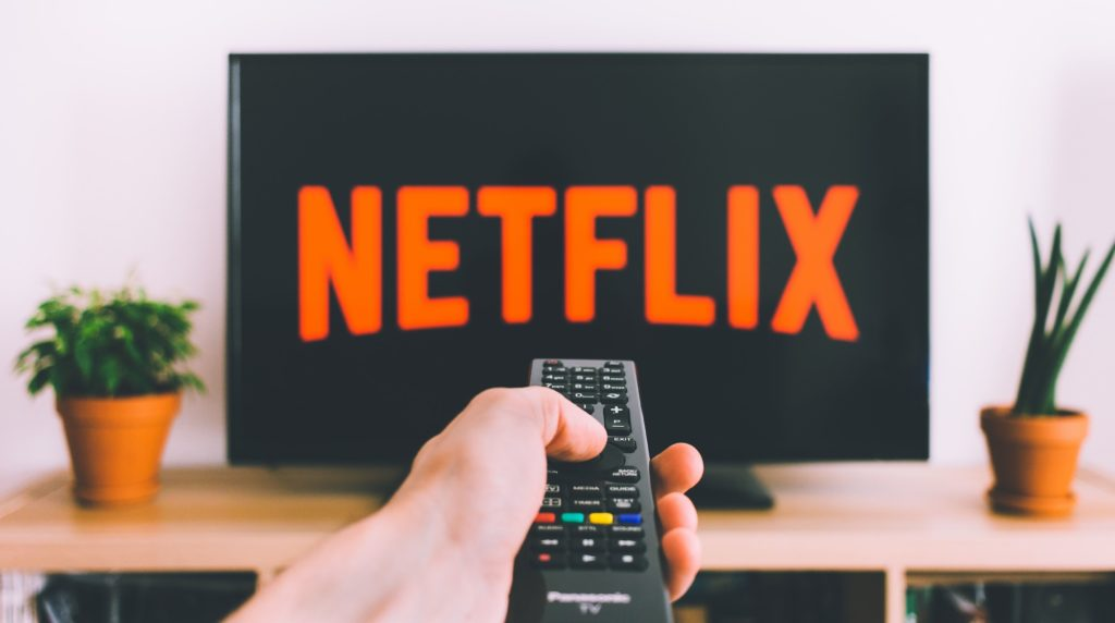 Close up of a hand pointing a remote at a TV displaying the Netflix channel