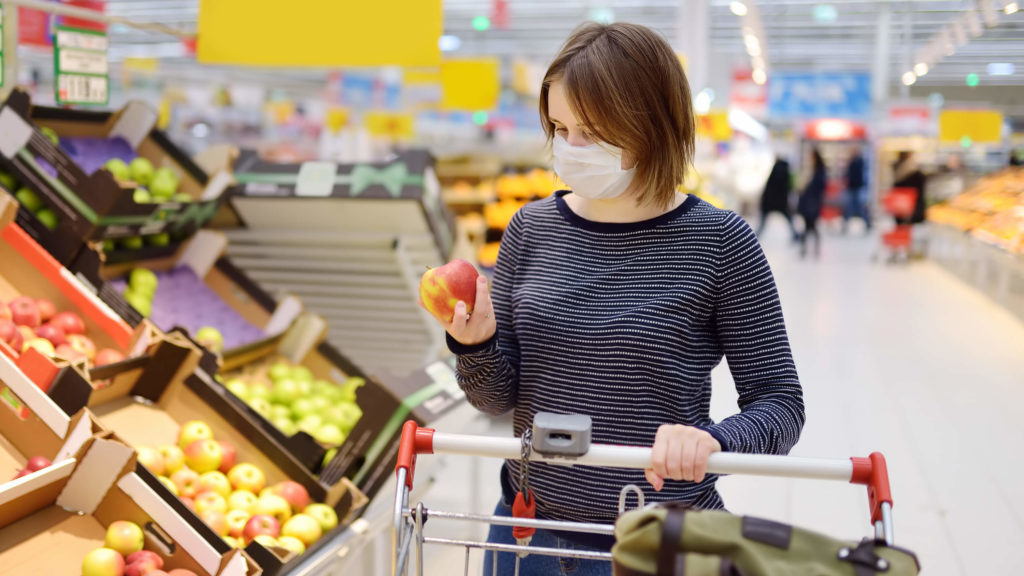 a woman wearing a surgical mask shops at a grocery store