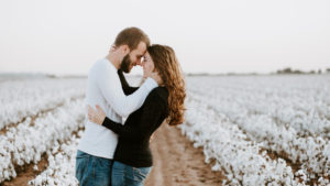 Engaged couple in field processing postponed wedding plans