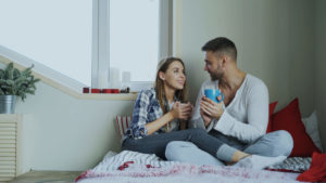 Young couple sitting on their bed drinking coffee and talking