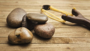 Close up of five smooth stones and a wooden slingshot lying on a wooden table