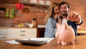 a man and woman add money to a piggy bank