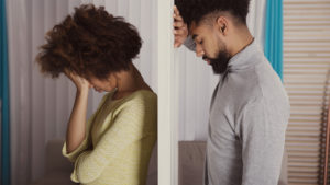 Profile shot of depressed-looking black couple separated by a wall, with each leaning against it from their respective side