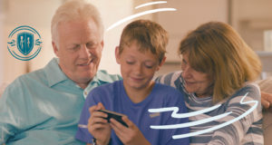Boy flanked by his grandparents as they sit on a couch. They're all looking at a mobile device he's holding.