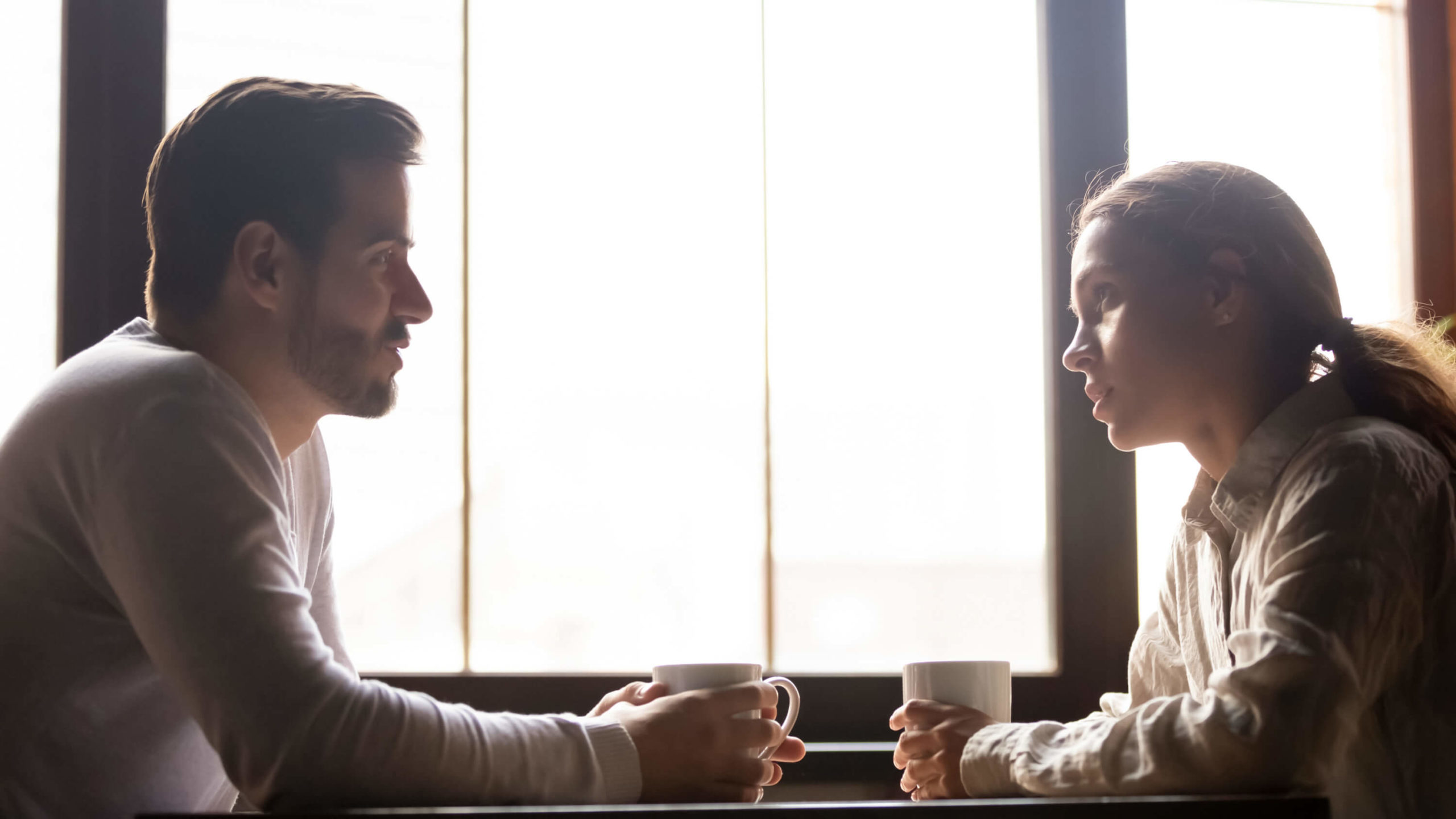 A young man and woman sit at a table and talk over a cup of coffee