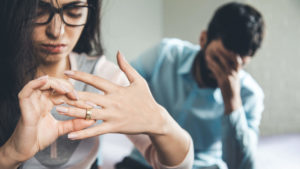 wife removing wedding ring to signal divorce