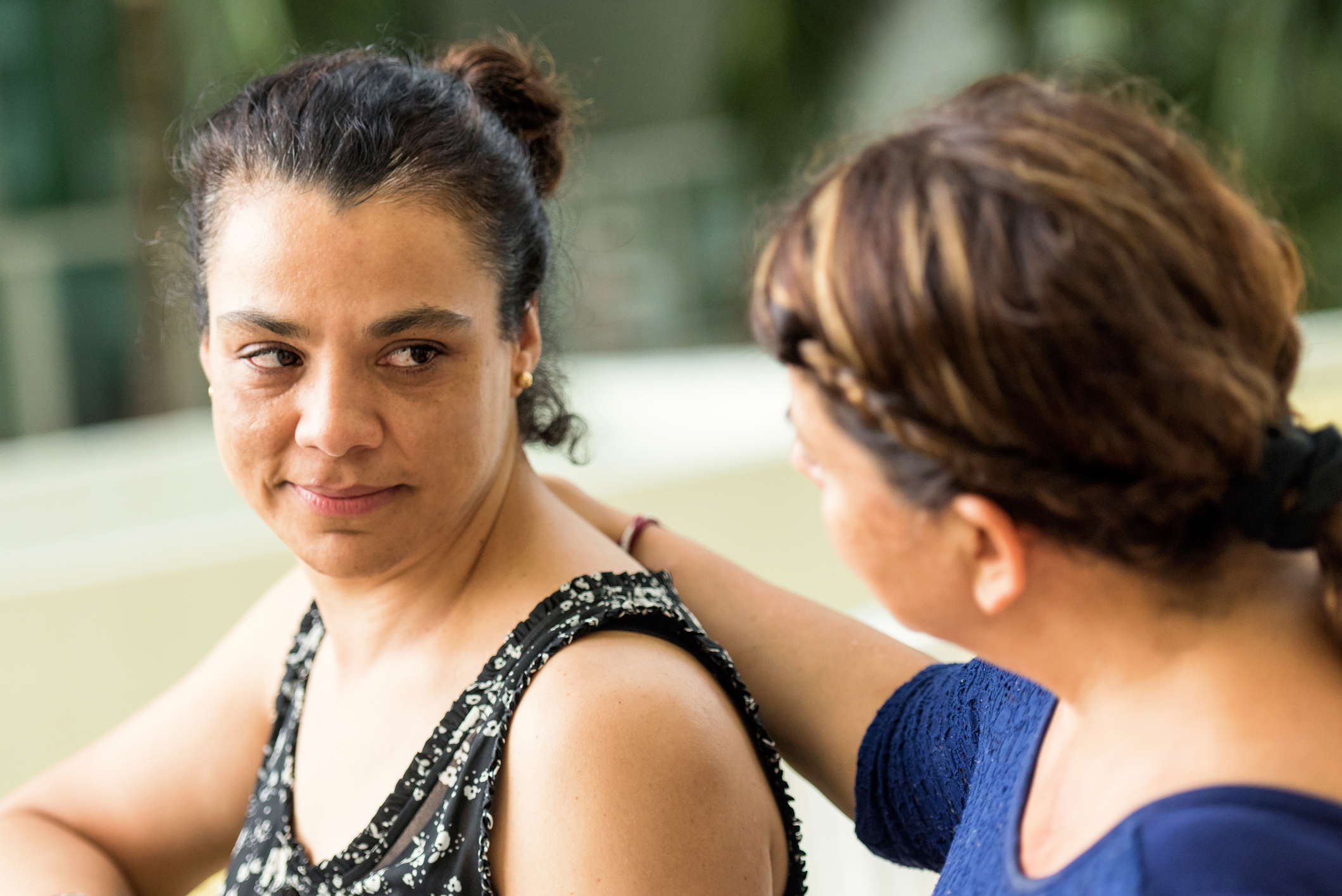 Close up of two women, one offering the other a compassionate arm around her shoulders