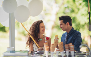 A young couple smiles at each other while they eat ice cream