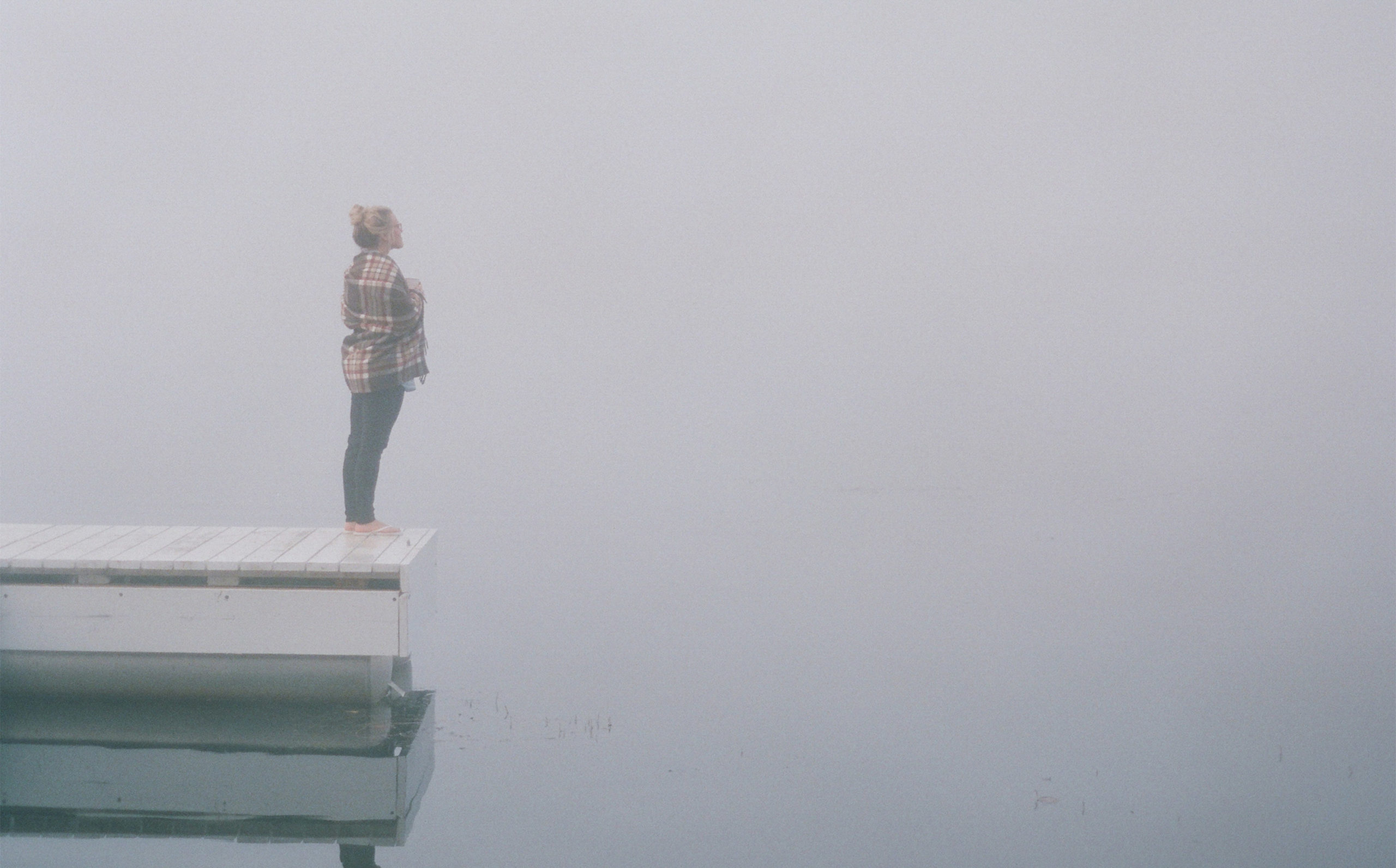 A woman standing at the end of a pier in fog.