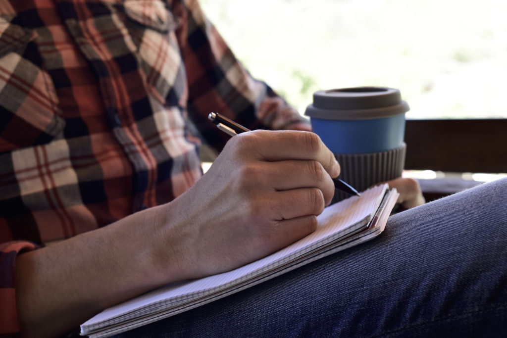Close up of a man's hand writing in a notebook; he's casually dressed and holding a cup of coffee in the other hand