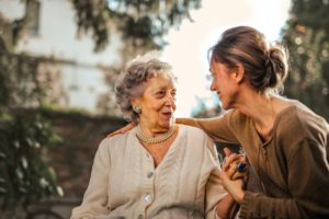 Joyful adult daughter greeting her happy, senior mother who's in a wheelchair