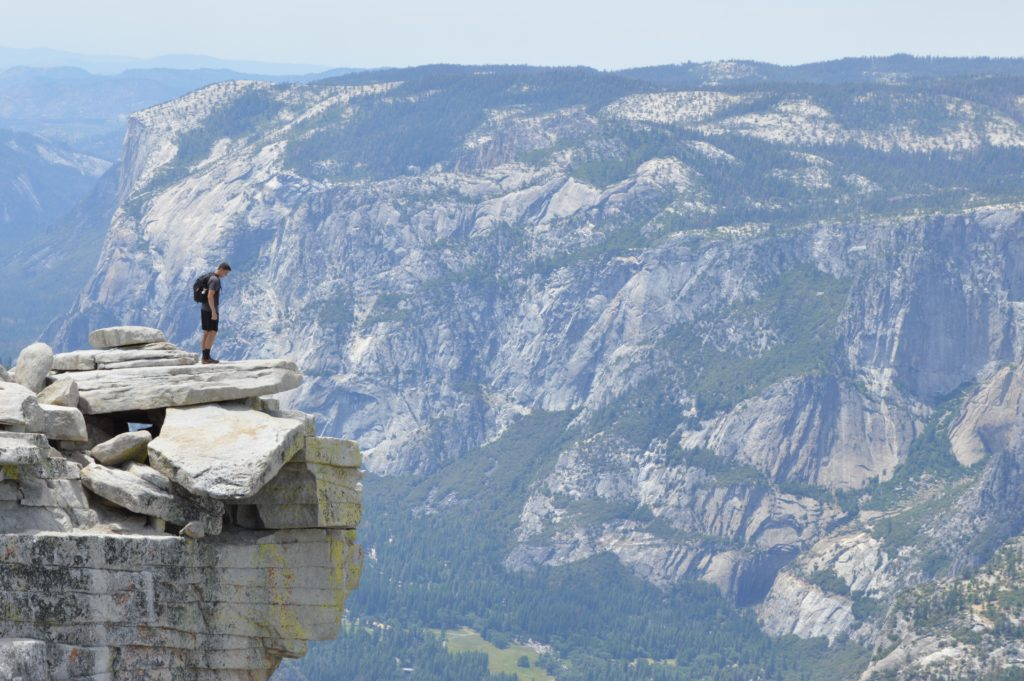 picture of a hiker standing high on rock cliff