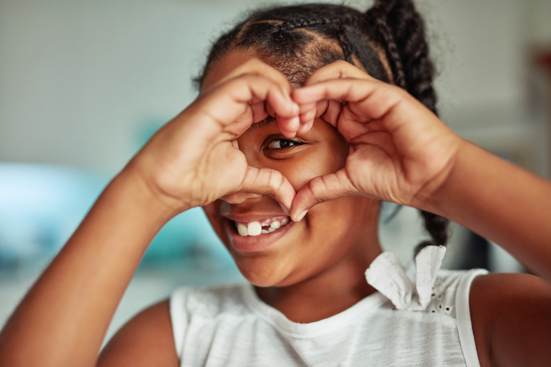 Close up of smiling black girl with one of her eyes looking through her hands which are in a heart shape
