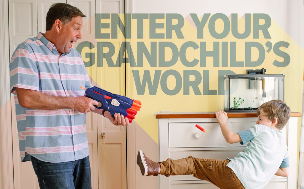 Grandpa shooting toy gun at grandson who's trying to dodge the foam dart, with the phrase 'Enter Your Grandchild's World'
