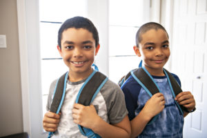 two boys in foster care with backpacks