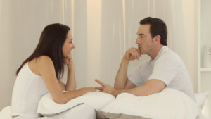 a woman and a man talk to each other while leaning on pillows