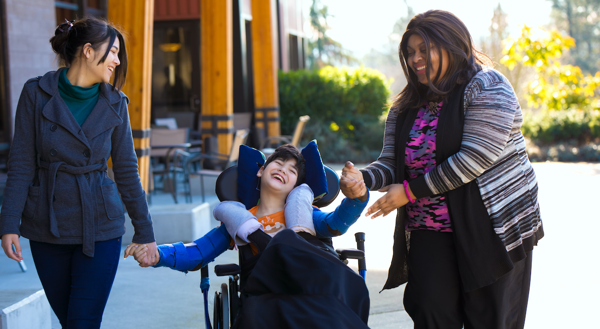 Two women help a child with special needs with how to engage with God.