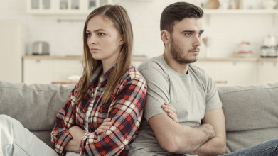 a young woman and man sit back to back after an argument