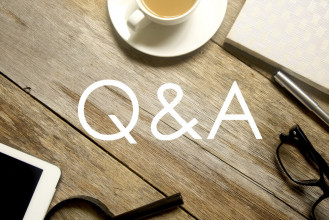 The letters 'Q&A' (for questions and answers) superimposed over an image of a table with a cup of tea and personal effects