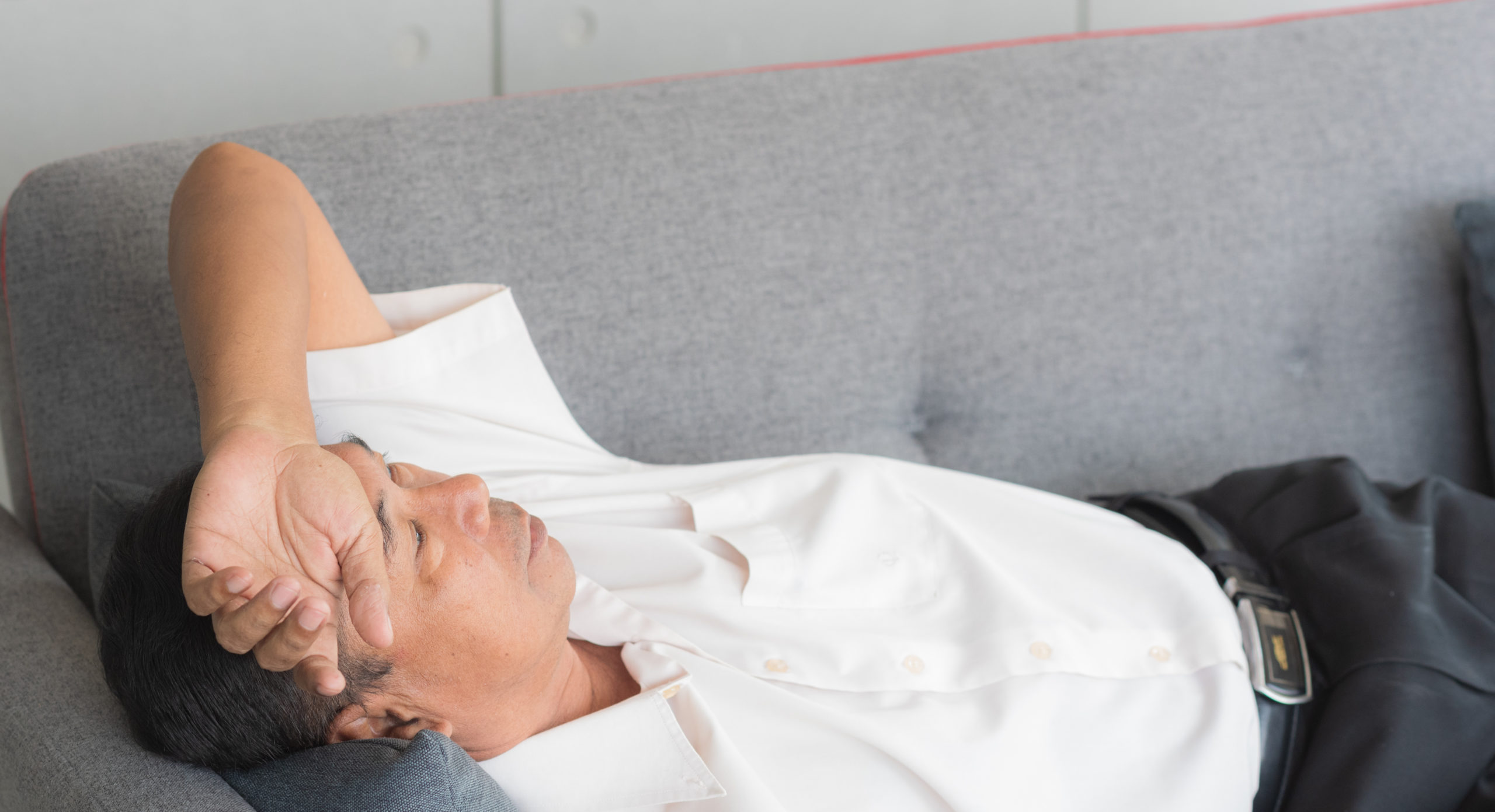 Senior Asian man sleeping on couch feeling sick and migraine from tired and health problems