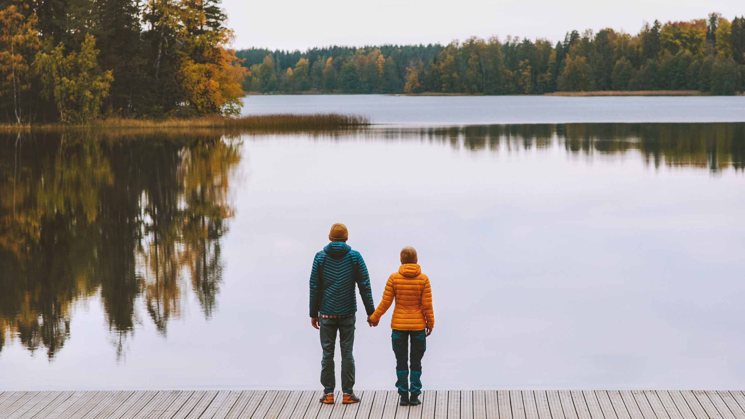 Couple holding hands looking out at autumn trees surrounding lake