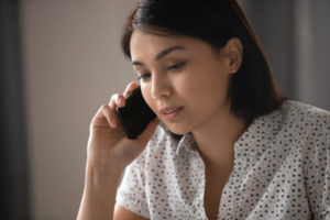 Close up of a young, pensive Asian woman listening to someone talking to her on her phone
