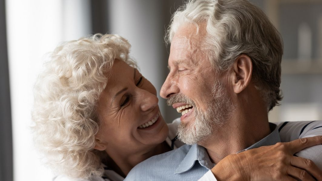 an older man hugging a woman and laughing